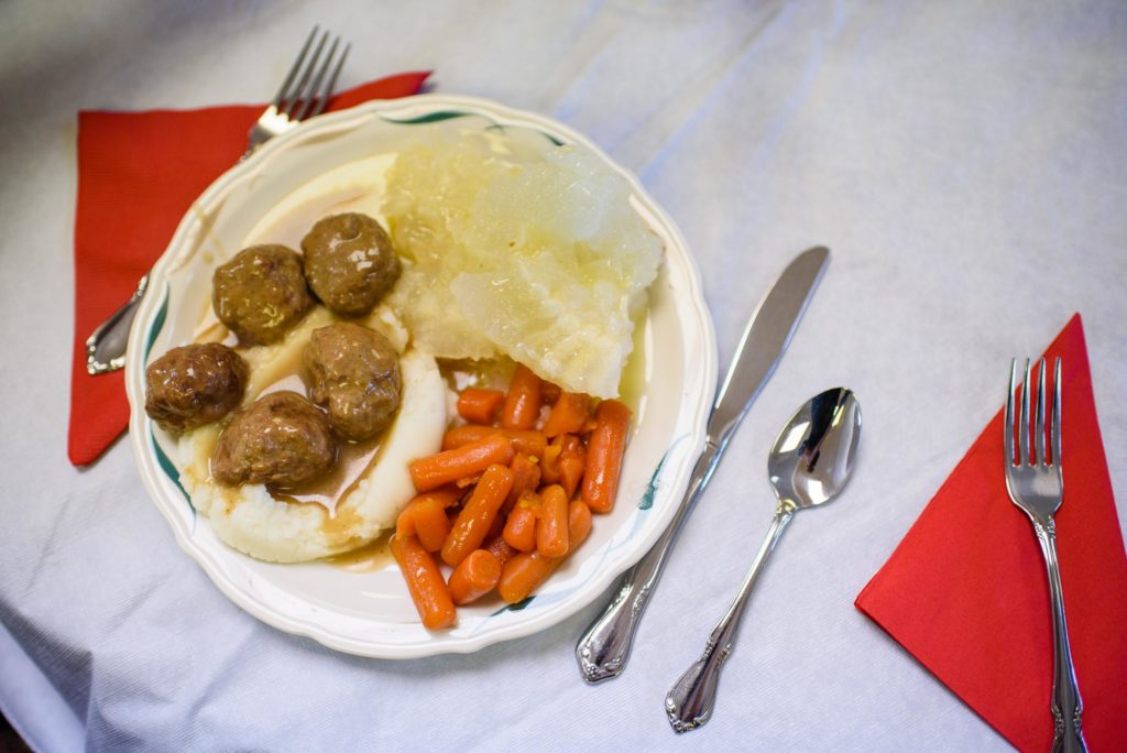 A full plate of potatoes, meatballs, sweet carrots, butter, and of course lutefisk.  Two scoops.