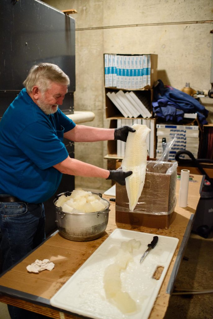 A volunteer cuts up the lutefisk to perfect serving sizes before boiling.