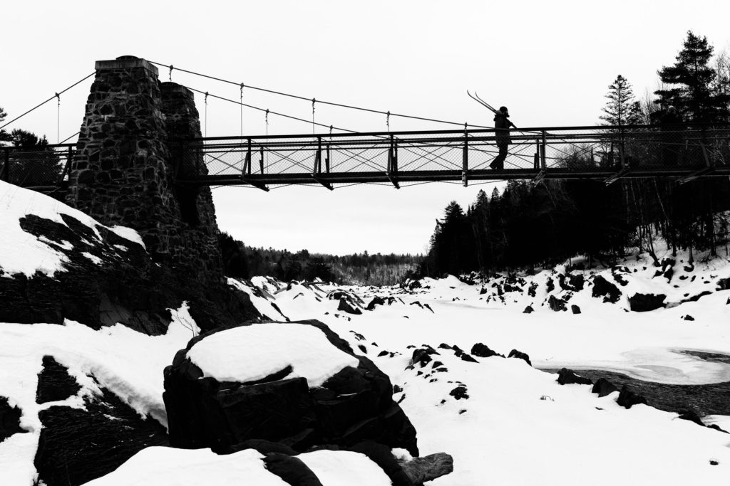 I walk with skis on the Swinging Bridge at Jay Cooke State Park.