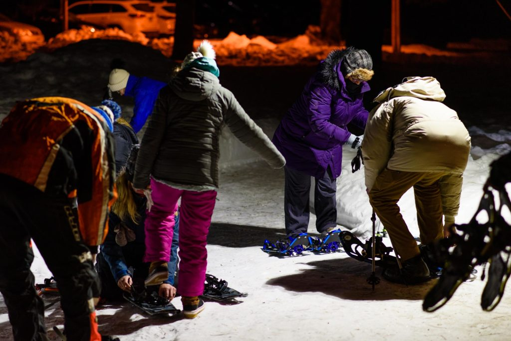 Everyone helps everyone get their snowshoes on before heading out into the frigid forest underneath the light of a full moon.