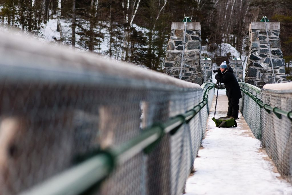 Another photographer braves the cold temperatures to get photos on the Swinging Bridge at Jay Cooke State Park.