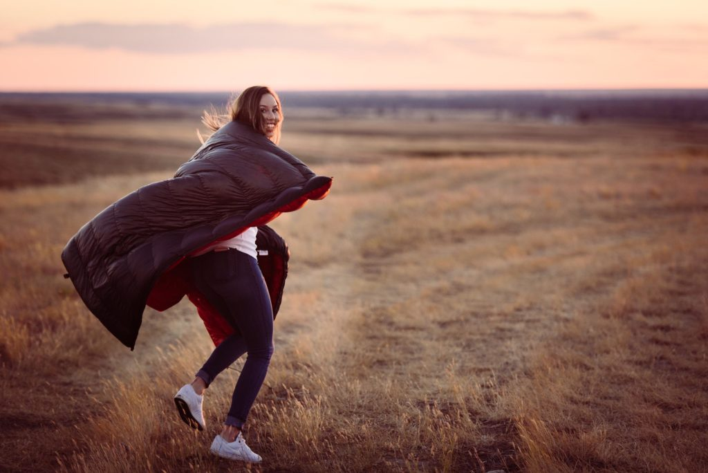 Girl runs away into Montana sunset with Enlightened Equipment's Revelation quilt.