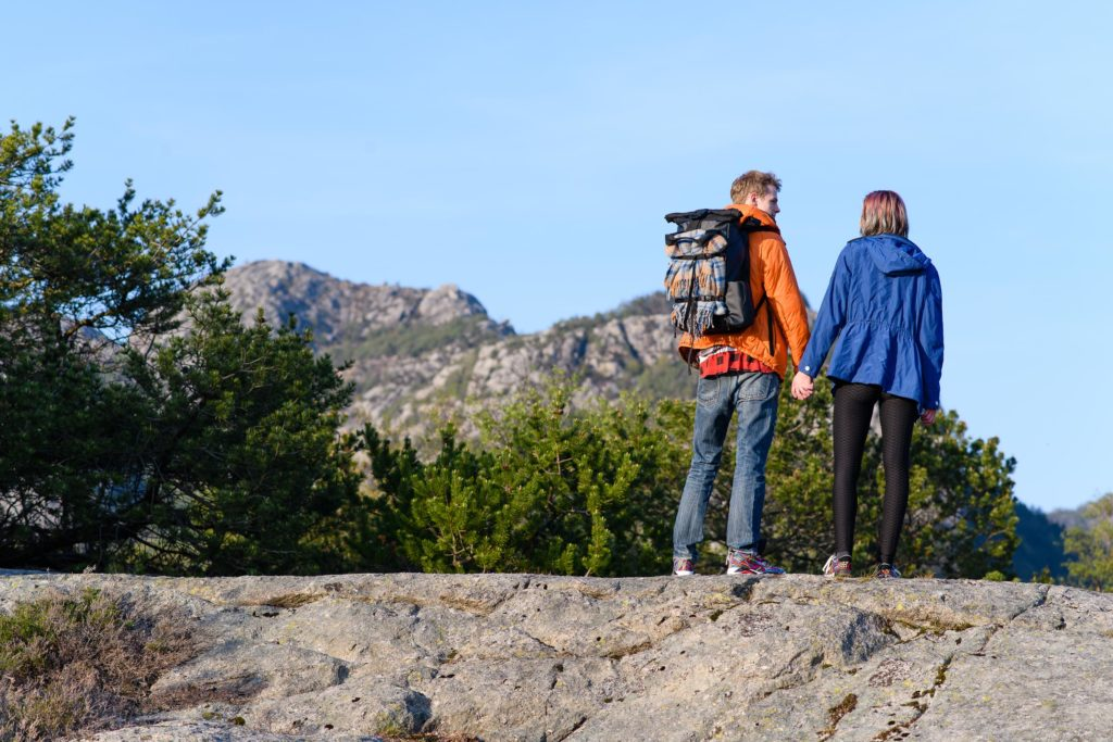 Hipster has blanket attached to back of backpack while hiking around in Norway.